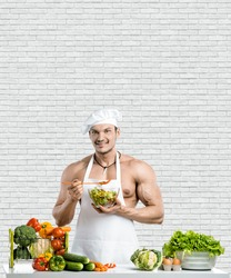 Man bodybuilder in white toque blanche and cook protective apron, concoction vegetables and smile, on white brick wall background. Healthy diet concept