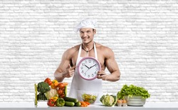 Man bodybuilder in white toque blanche and cook protective apron, hold watch , on white brick wall background. Healthy eating concept