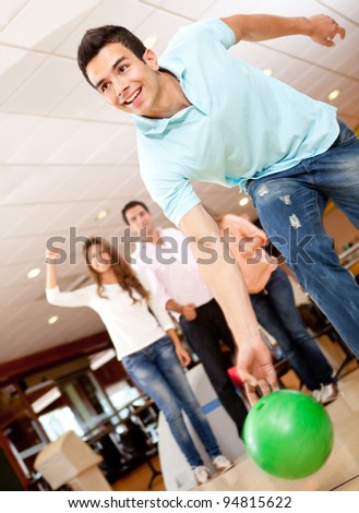 Man bowling and his friends cheering at the background