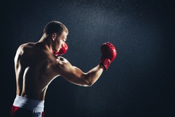 Man boxing with red gloves on his hands in the rain. Professional fighter, boxer.