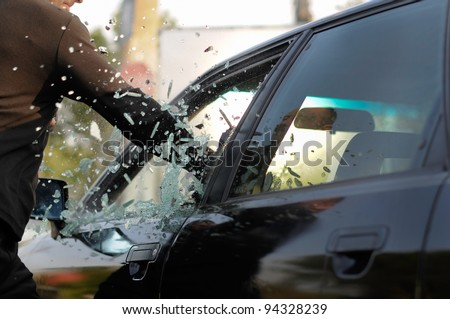 Man breaking a car's window in a million of pieces