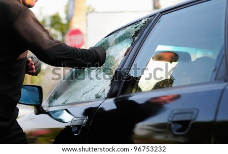 man breaking car window
