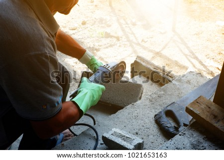 Man Bricklayer Is Cutting Cement Brick Block With Small Cutter Machine For Wall Construction In New