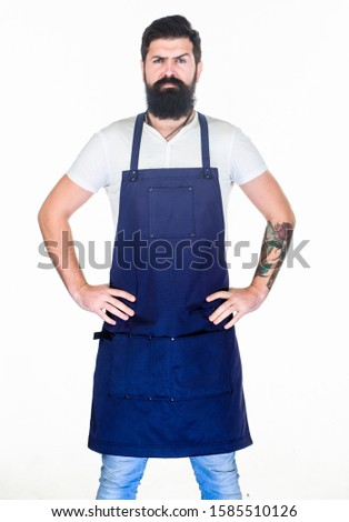 Man brutal bearded hipster with mustache wear apron uniform. Barbershop staff. Beard grooming salon. Well groomed macho barber. Hipster style. Barbershop concept. Hairdresser barber salon for men.