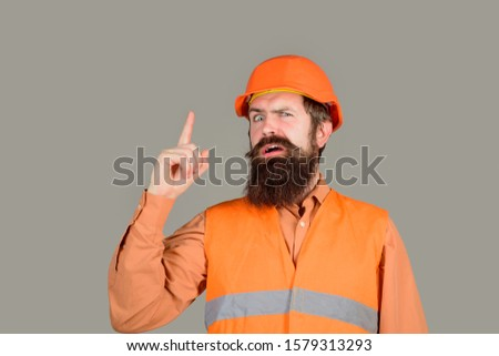 Man builder having good idea. Builder in protective clothing and helmet. Engineer warns of danger lifting his finger up. Man builder in hard hat shows warning sign with finger. Builder in hardhat.
