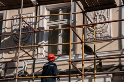 Man builder in orange construction helmet working from scaffolding to renovate historic building wall with ornate sculptural relievo details. Historic building restoration in progress