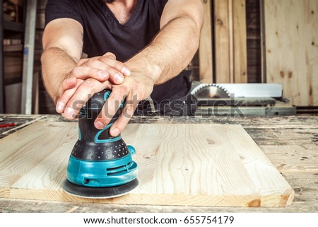 Man builder processes the board with a random orbit sander in the workshop #655754179