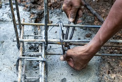 Man builder worker wires for knitting metal rods with steel bars ,pillars for concrete