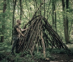 Man building a  survival  shelter in the forest. Shelter in the woods from tree branches.