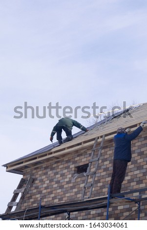 man builds a new house roof