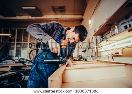 Man builds furniture in the carpentry shop. Man collects furniture details in the carpentry shop. Toned image. Uses a professional stapler or nail gun. from the side view close