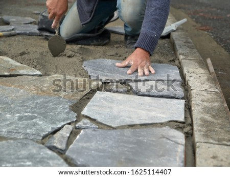 Man builds / places sidewalk from natural stones