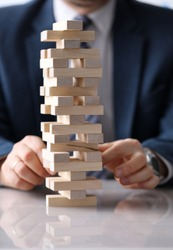 Man business suit stacks board game wooden blocks. Close up male hands stack wooden blocks on white table. Employee develops ingenuity, sleight hand and sense balance with help board game.