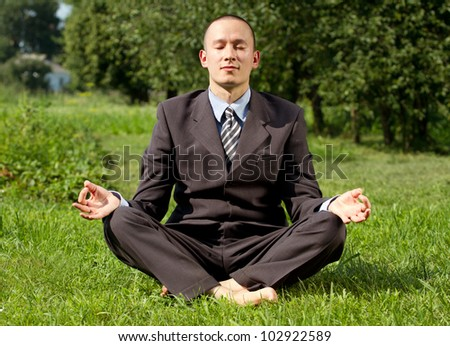 Man businessman meditating outdoors in lotus pose