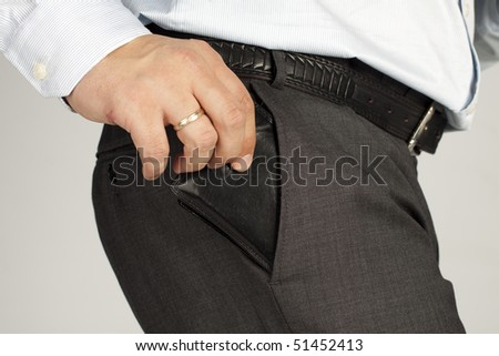 Man businessman pulls the wallet from his trouser pocket, close-up