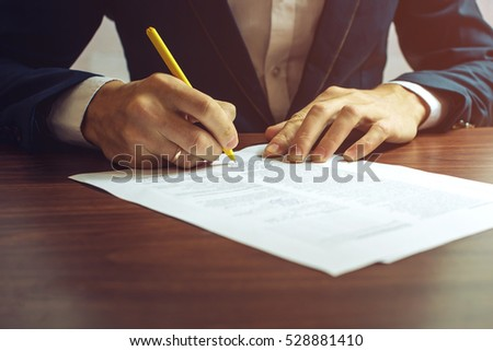 Man businessman signs documents with a pen making the signature sitting at the desk in the light. With retro effect. #528881410
