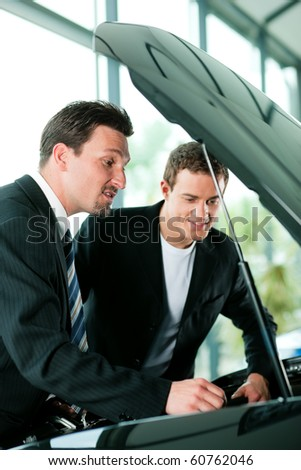 Man buying a car in dealership looking under the hood at the engine