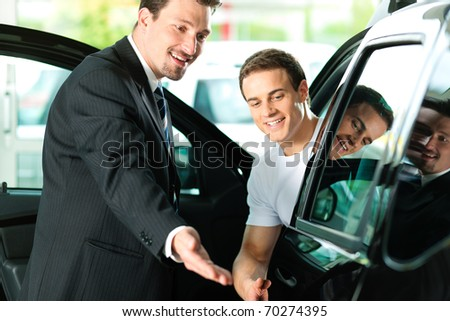 Man buying a car in dealership sitting in his new auto, the salesman talking to him and explaining details - stock photo