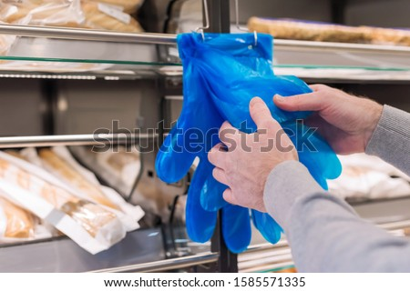 Man buying bread and wearing disposable glove in grocery shoping or pastry shop