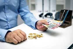 Man buying gold jewellry, pawn shop and euro banknotes