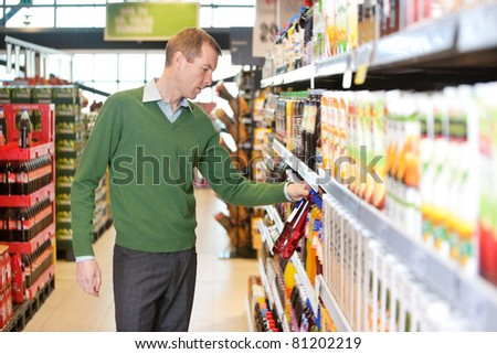 Man buying juice in the supermarket - stock photo
