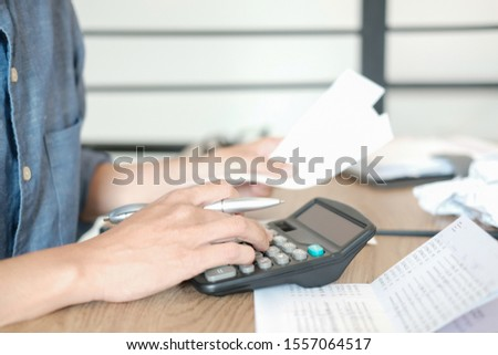 man calculate domestic bills. Businessman with calculator checking balance & costs. Startup counting finance for paying taxes at office