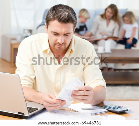 Man calculating his bills while his family are on the sofa