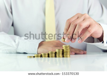 Man calculating stack of gold coins in one row