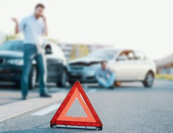 Man calling first aid after a bad car crash on the road,main focus on red triangle