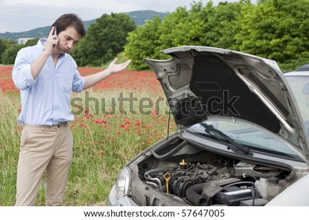 man calling the repair service after car breakdown