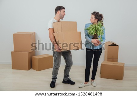 Man can not hold heavy carton boxes anymore, but he doesn't know where to put them and is shouting at his wife. His wife is standing with flowerpot in hands, happy face expression. #1528481498