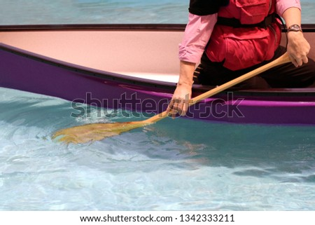 Man canoeing close up. Purple canoe in bright clear water.
