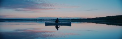 Man canoeing in a traditional wooden boat on a large lake at dawn