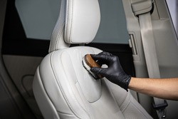 Man car detailing studio worker cleaning car leather seat with a brush.