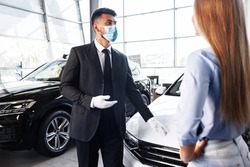 Man car salesman in face mask talking to a client in showroom
