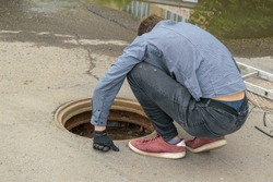 Man carefully looks at  open Manhole. Squatting bent over. View from the back. Concept of eliminating accident, laying communications, communication wires.