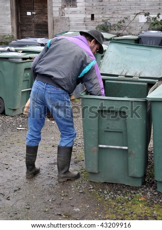 Man carefully placing glass bottle in recycle bin. This can also be used for a trash bin concept