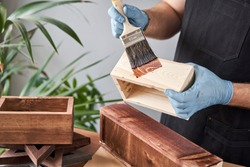 Man carpenter varnishing wooden crate for flowers with brush in her small business woodwork workshop. In your work, do you use stains or wood preservatives to show the wood pattern.