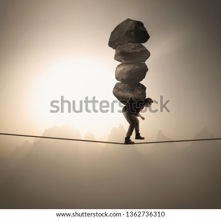 Man carries a stack of big rocks while balancing on a rope at high altitude . #1362736310