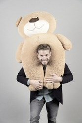 Man carries giant teddy bear on neck, grey background. Birthday gift concept. Teddy bear plush toy pleasant surprise. Guy happy bearded face holds toy teddy bear. Man formal suit cute gift surprise.