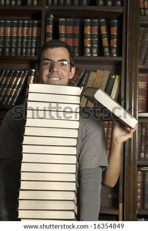 Man carries stack of books in library. Woman stands behind him with exposed arm holding a book. Vertically framed photo.