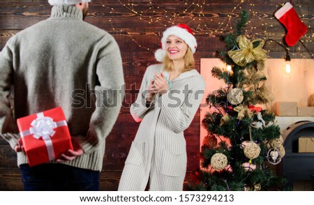 Man carry gift box behind back. Woman smiling face santa. Christmas surprise concept. Giving and sharing. Generosity and kindness. Surprising his wife. Prepare surprise for darling. Winter surprise.