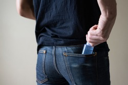 Man carry sanitizer hand gel bottle in pocket jeans for prevention coronavirus and germ, new normal concept