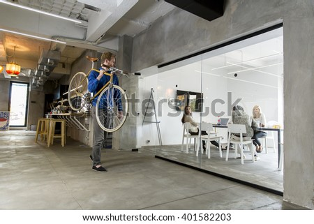 Man carrying a bicycle in the office #401582203