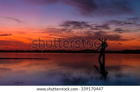Man carrying a cross on a lake, with a fire like sunset in the sky. Stock photo ©