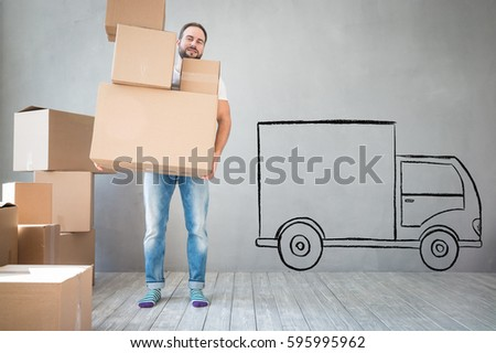 Man carrying boxes into new home. Moving house day and express delivery concept #595995962
