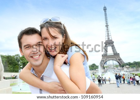 Man carrying girlfriend on his back in front of Eiffel tower