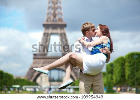 Man carrying his girlfriend in his arms in Paris - stock photo