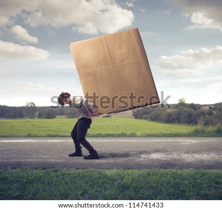 Man carrying on his shoulders a large box
