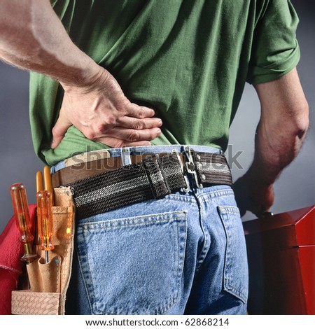 man carrying toolbox while rubbing back
